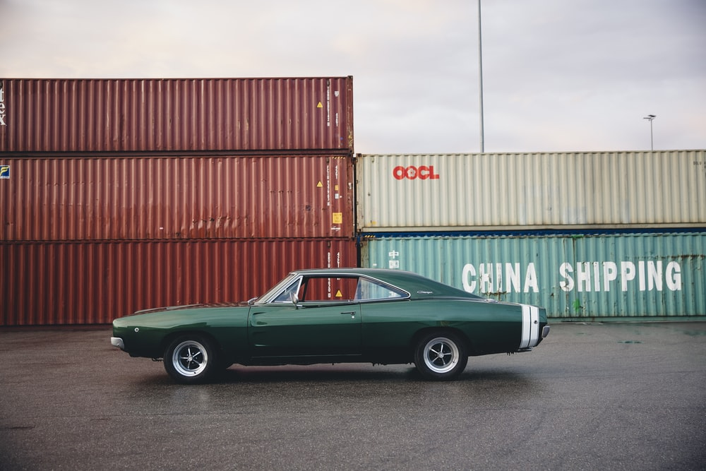 green coupe beside intermodal containers