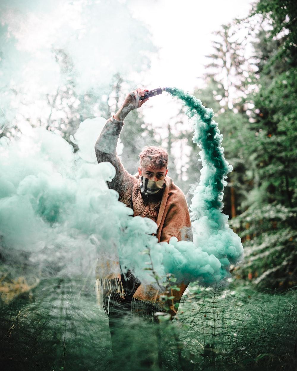 man holding blue ash smoke