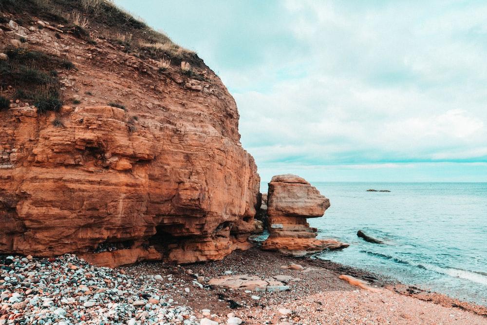 brown rocky mountain beside beach