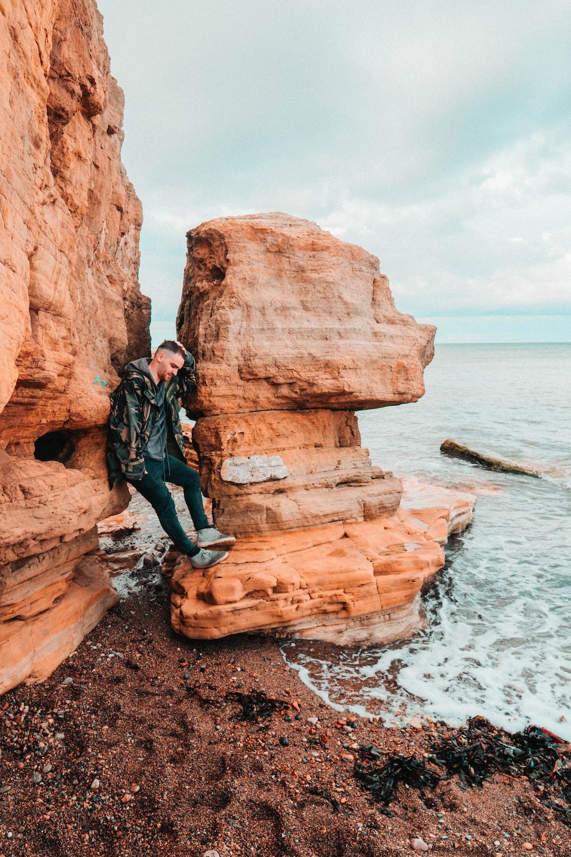 man standing on brown rock beside beach