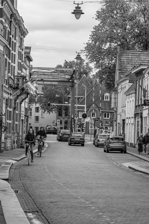 grayscale photo of people walking on sidewalk near buildings