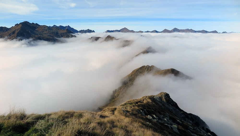 view photography of white fogs in mountain during daytime