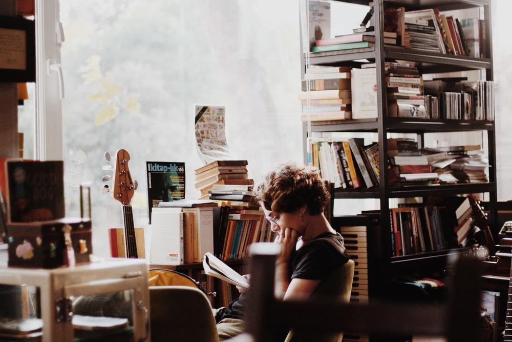 woman reading book sitting beside electronic keyboard