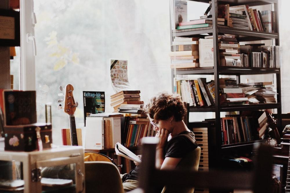 電子キーボードのそばに座って本を読む女