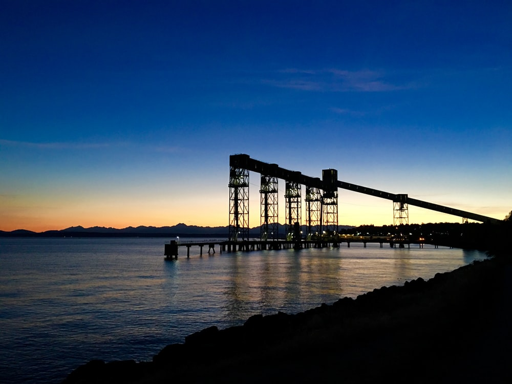 silhouette of towers and dock over water