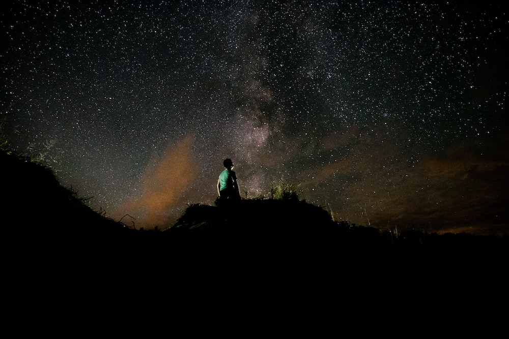 silhouette of person under clear night sky