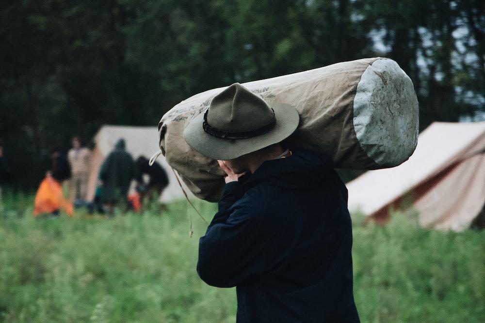 selective focus photography of walking man carrying bag near set-up tent