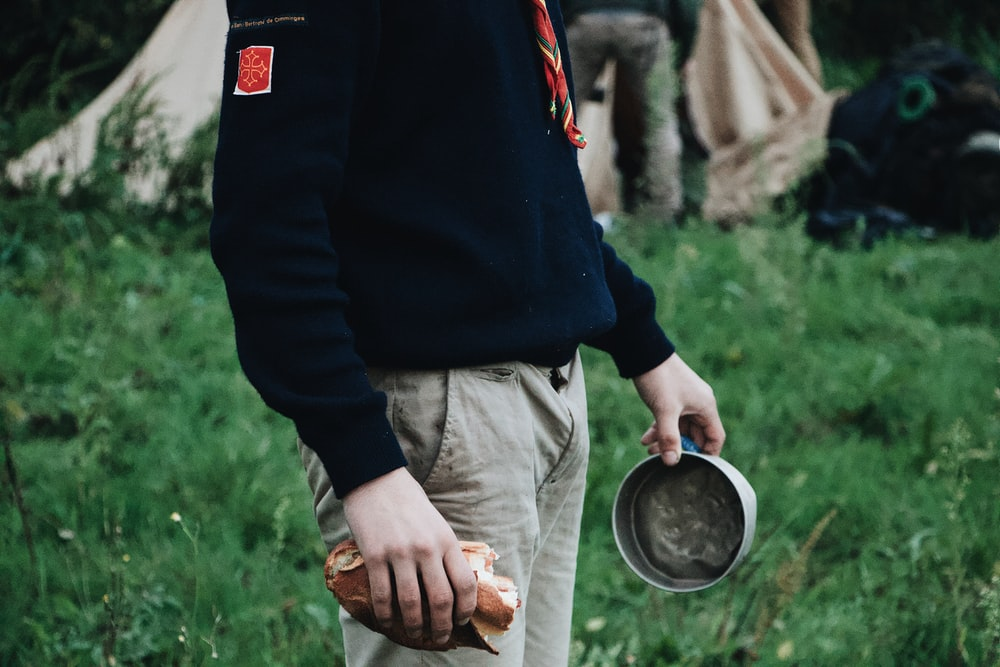person holding bread and gray metal bowl