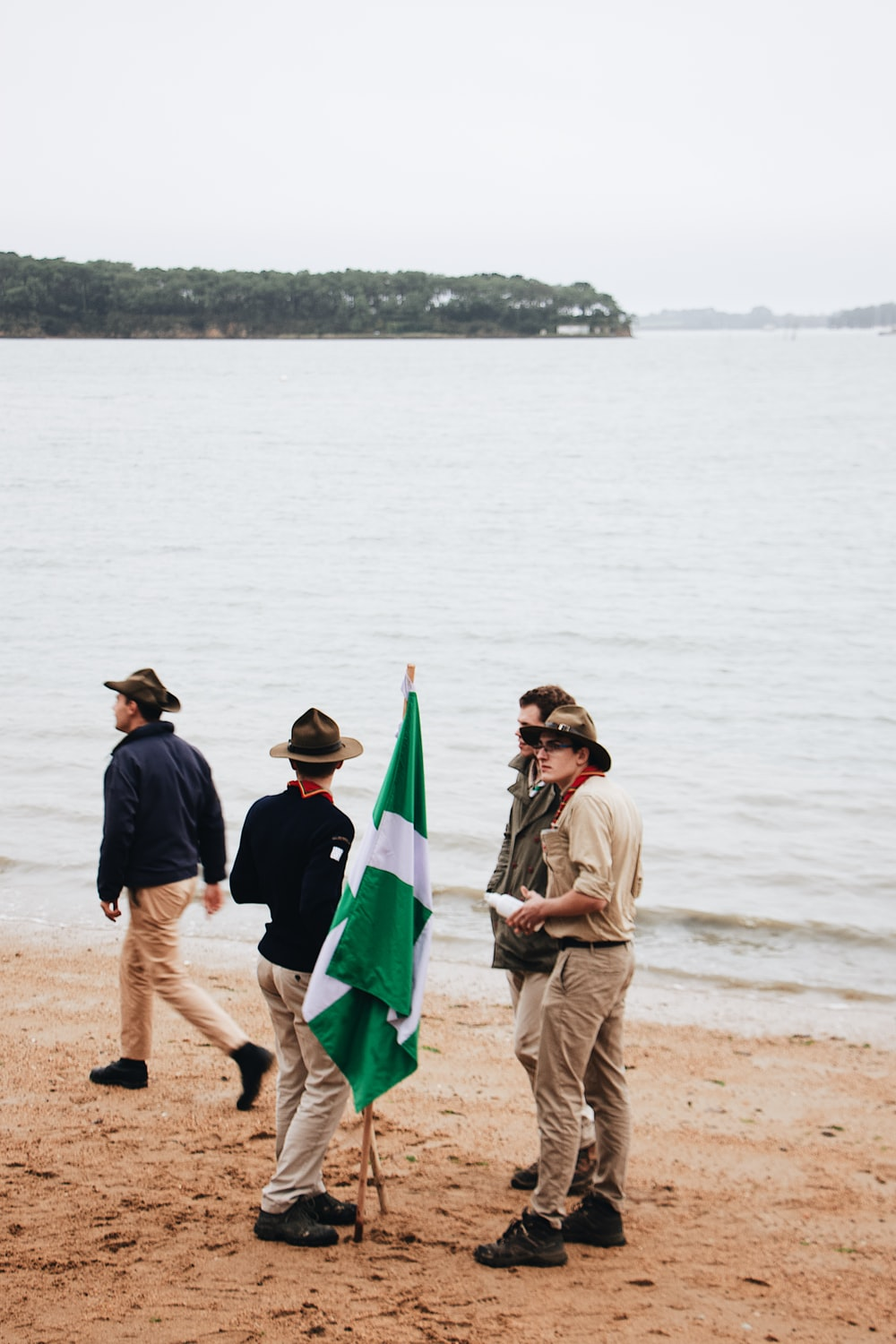 four men standing on shore near body of water