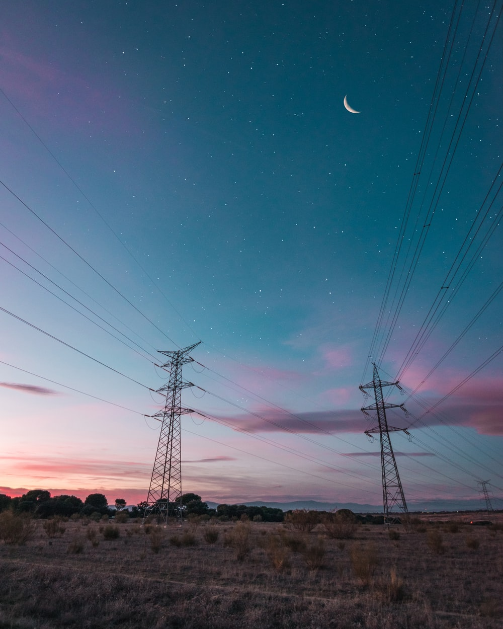black transmission towers under clear night sky