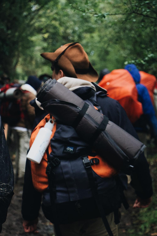 man carrying black sleeping bag and backpack