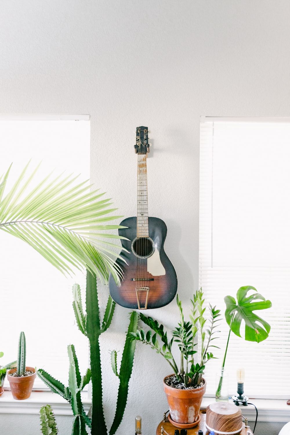 black and brown acoustic guitar hanging on wall