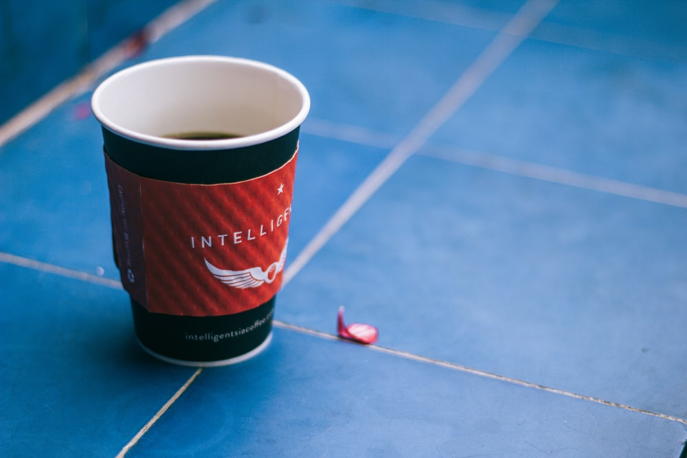 black and red disposable cup on blue surface