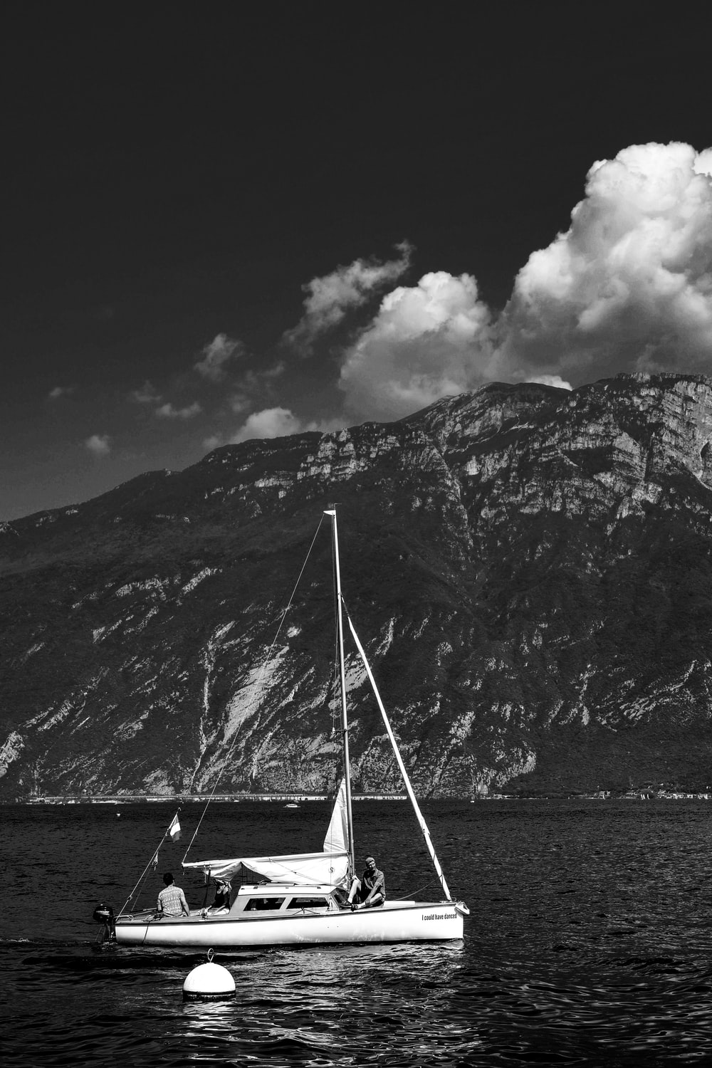 grayscale photography of sailing boat under cloudy sky
