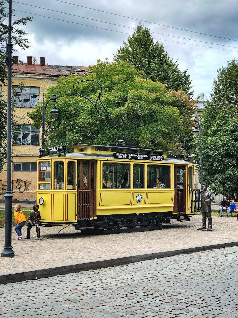 three statues beside yellow tram during daytime