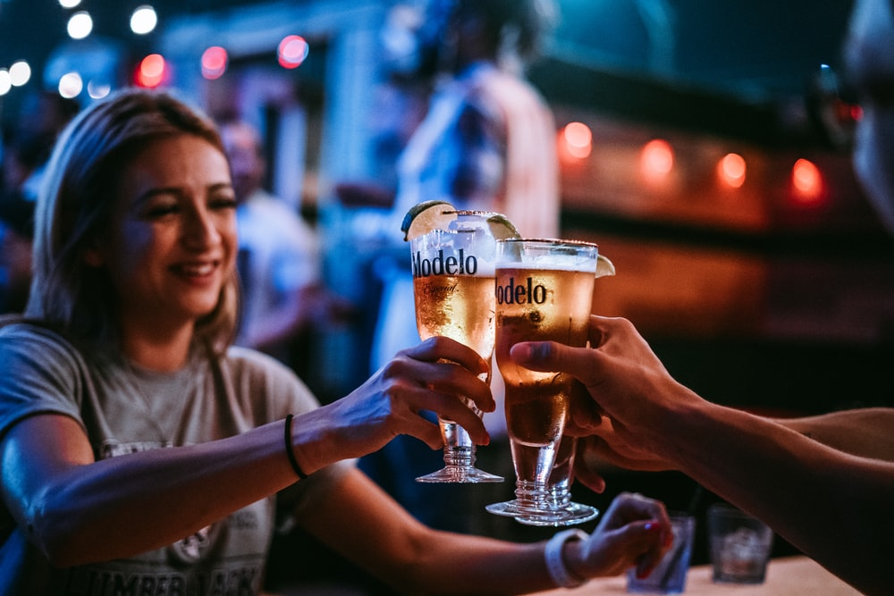 three persons toast their glasses at the bar