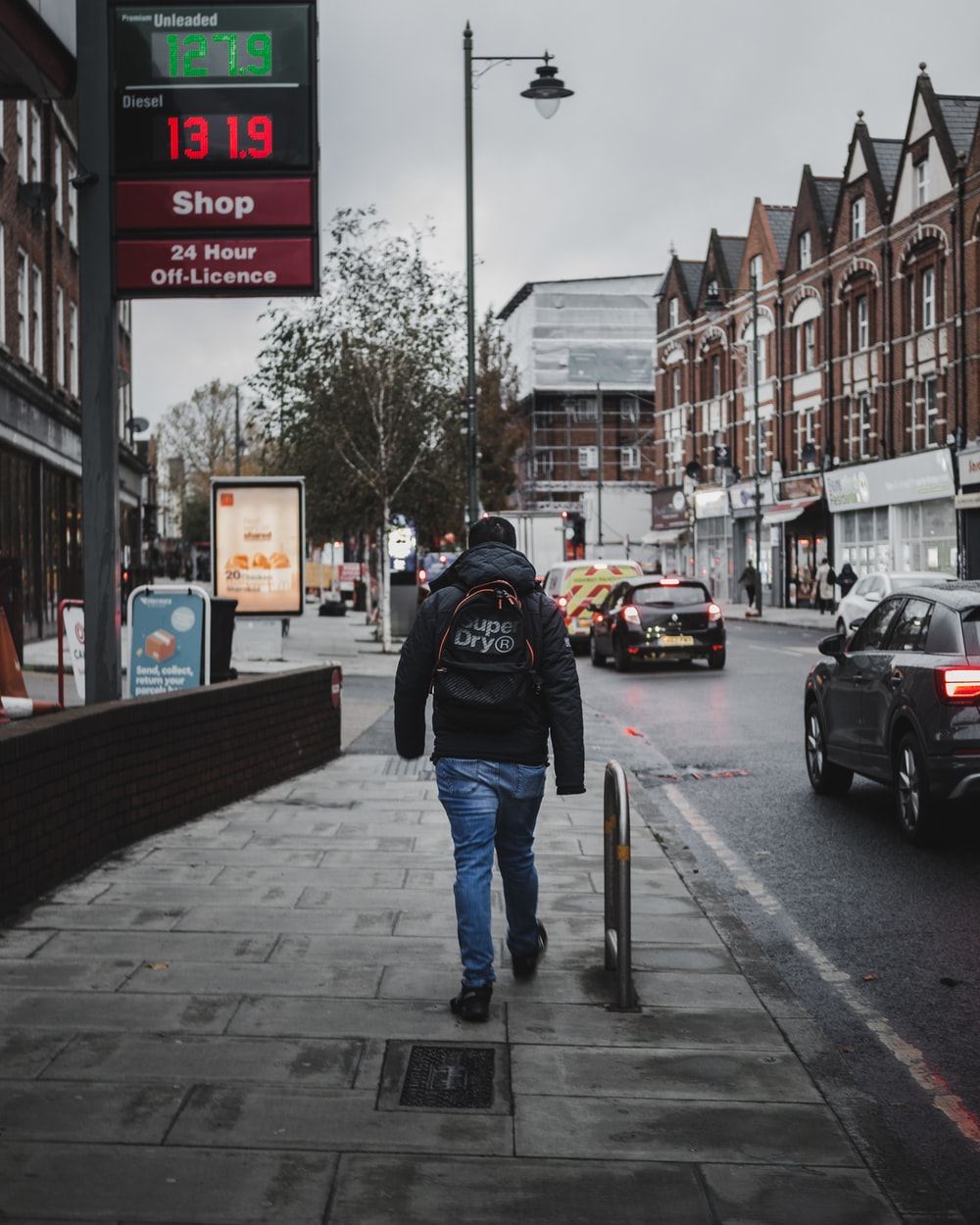 man in black hoodie walking beside road