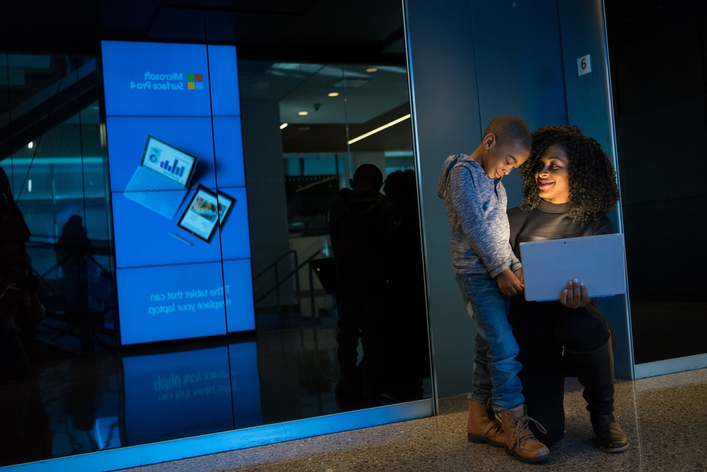 woman holding laptop beside boy in gray shirt