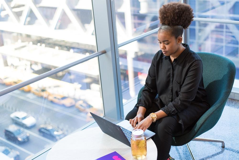 woman in black dress shirt using MacBook