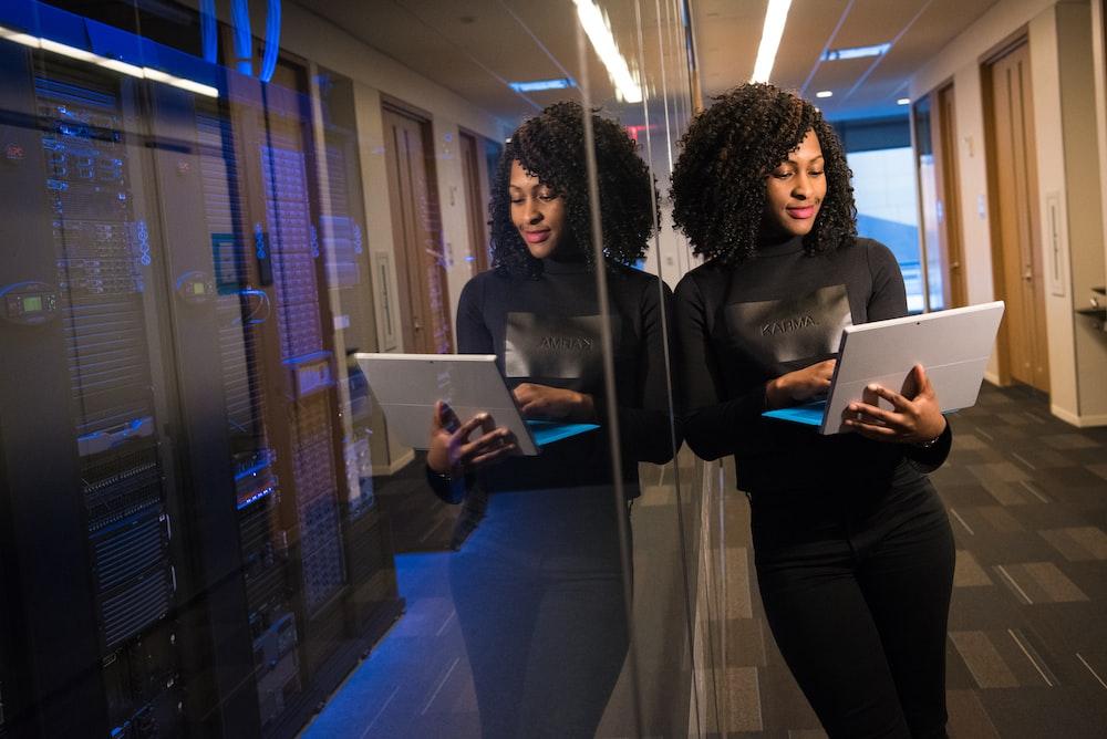 woman in black shirt using laptop computer