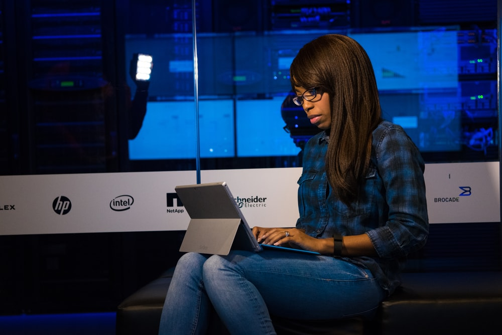 woman in blue and black plaid dress shirt using laptop computer