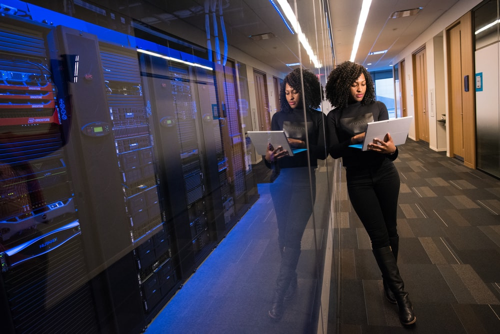 woman in black top using MacBook and a server room seperated by glass. A perfect representation of client-side vs server-side comparison in headerbidding