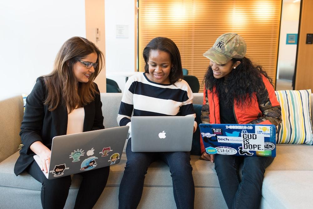 three women sitting on sofa with MacBook