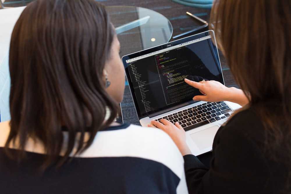 woman using MacBook Pro with person in white top
