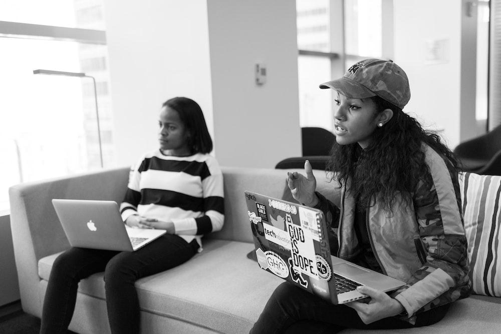 two women holding laptops