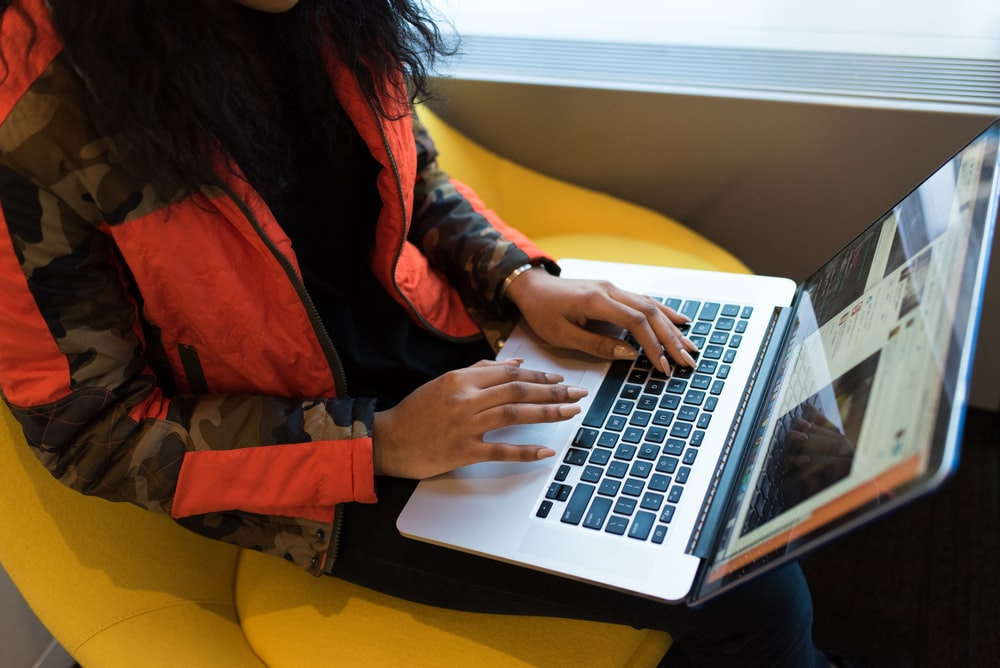 woman in red and black jacket using MacBook Pro