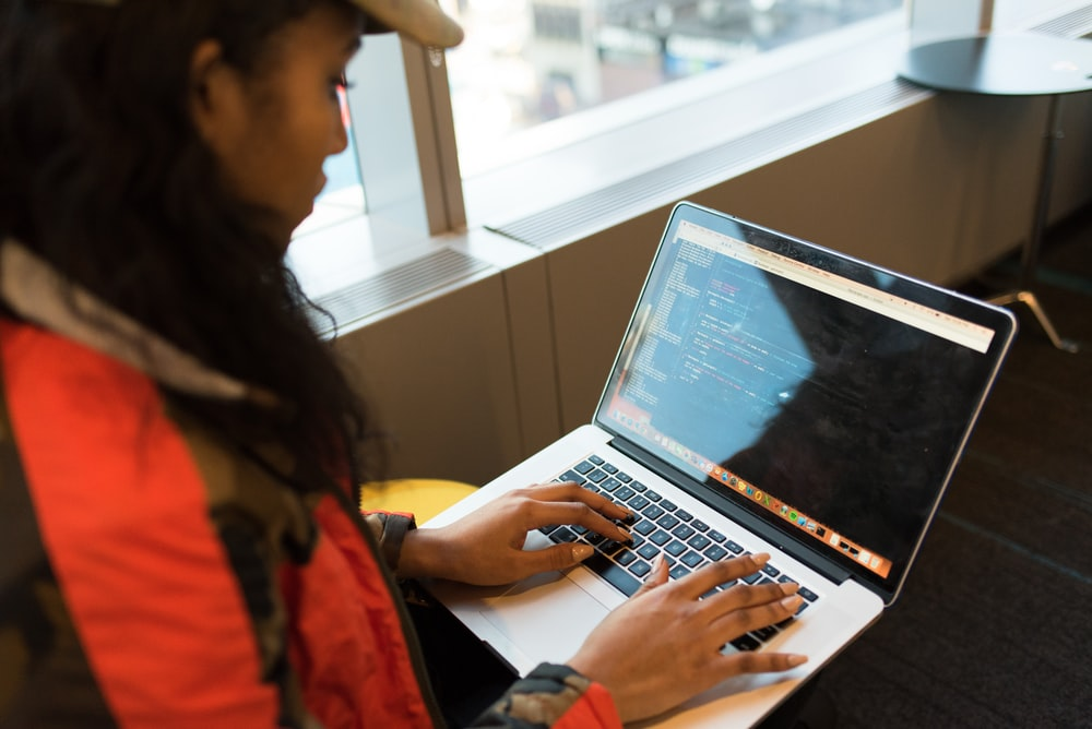 woman in red and black jacket using MacBook