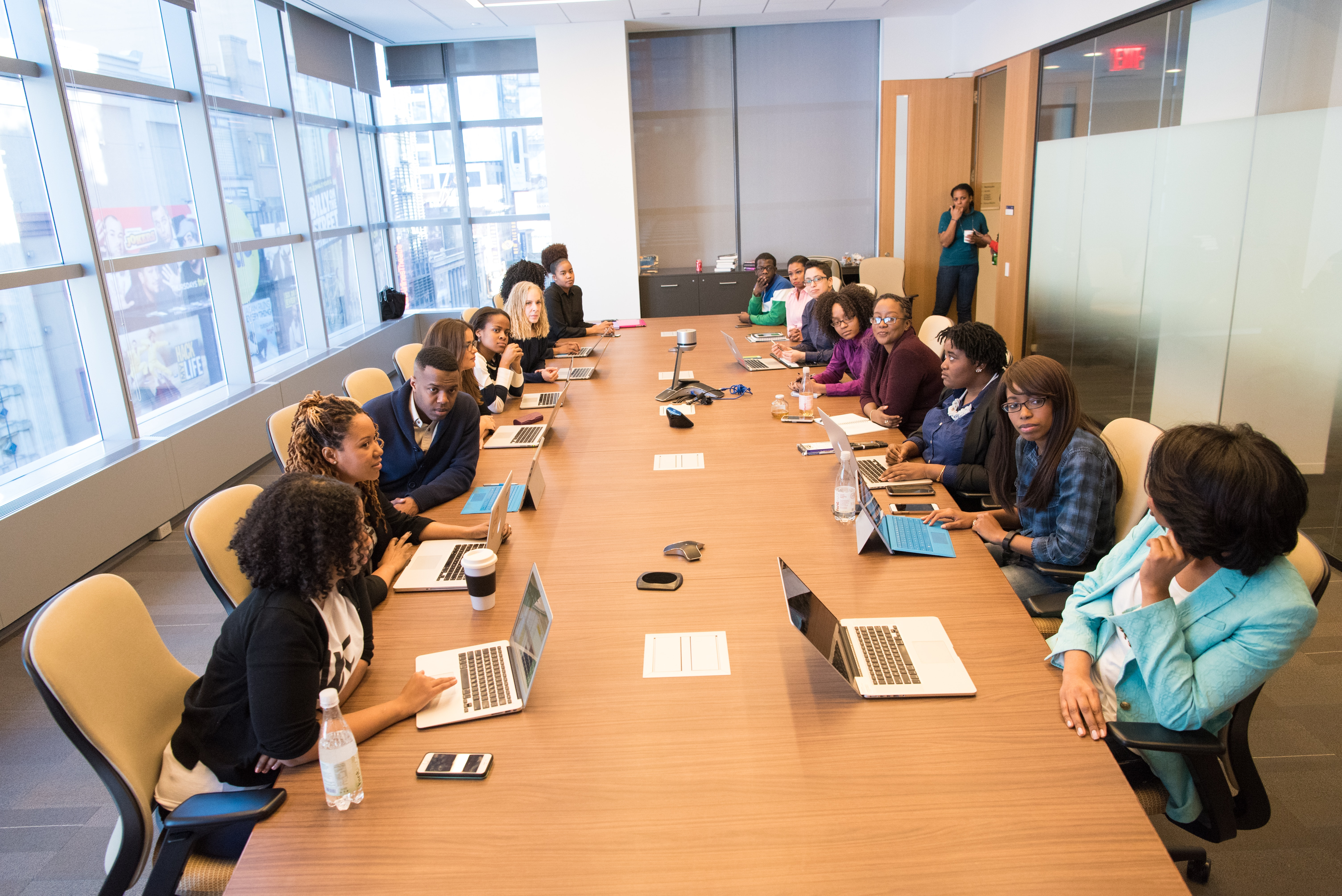 people sitting beside rectangular brown table with laptops