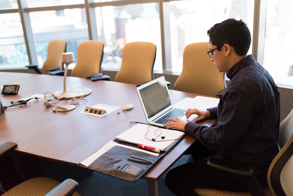 man uses laptop at the conference table