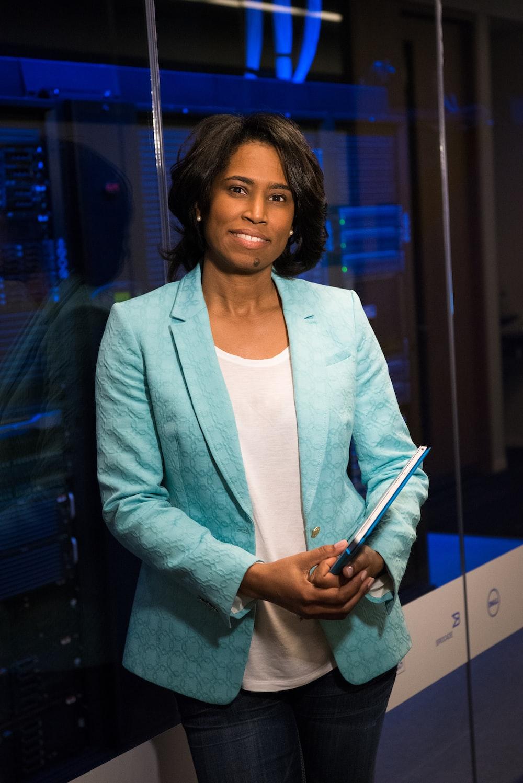woman in blue blazer standing beside glass wall