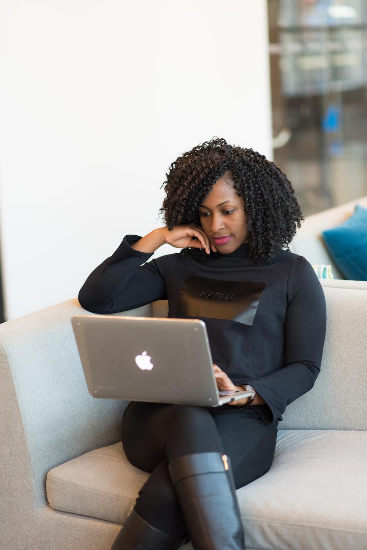 woman in black coat using MacBook