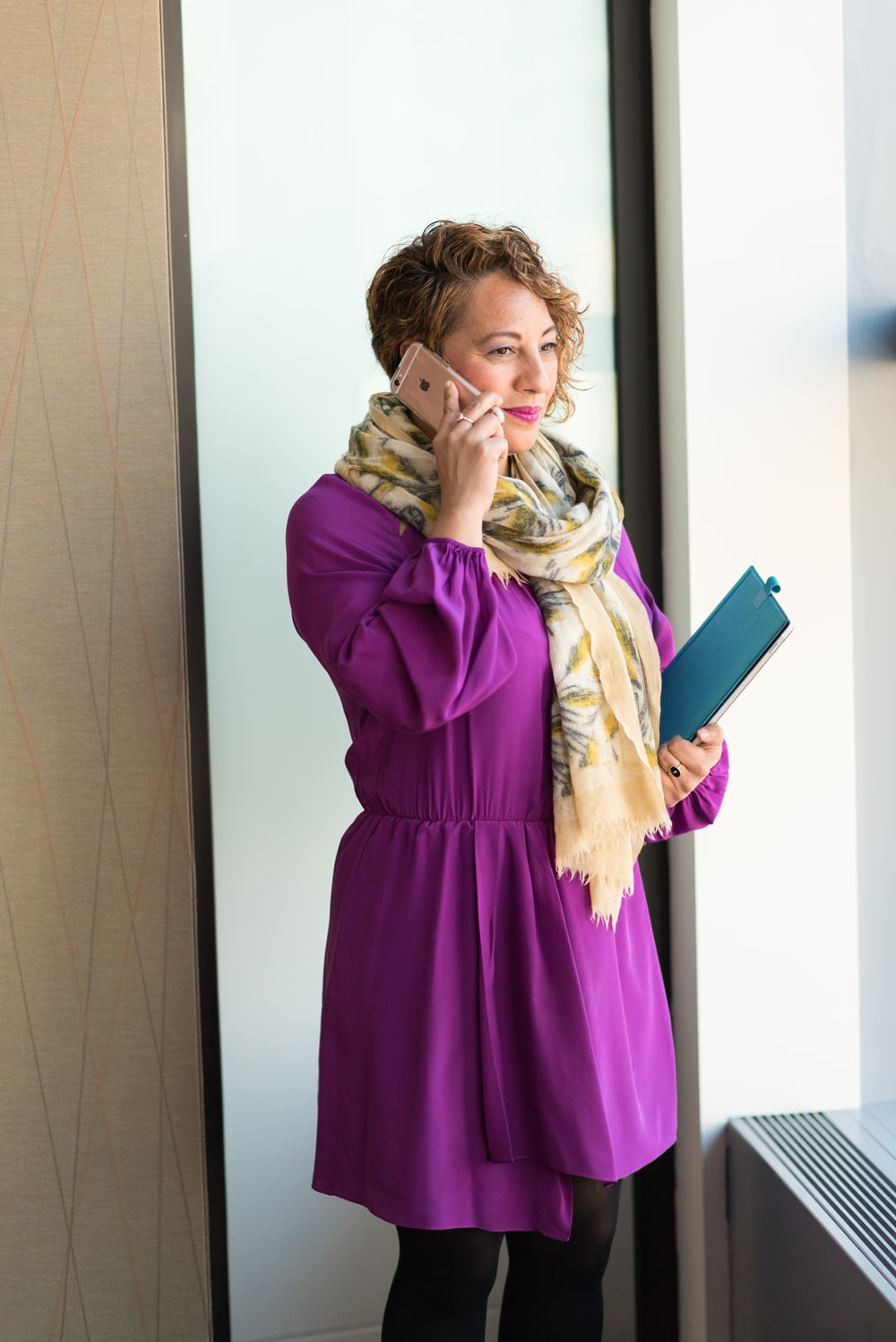 selective focus photography of standing woman wearing purple long-sleeved dress talking to the phone