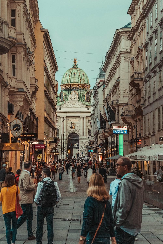 people walking between two buildings during daytime
