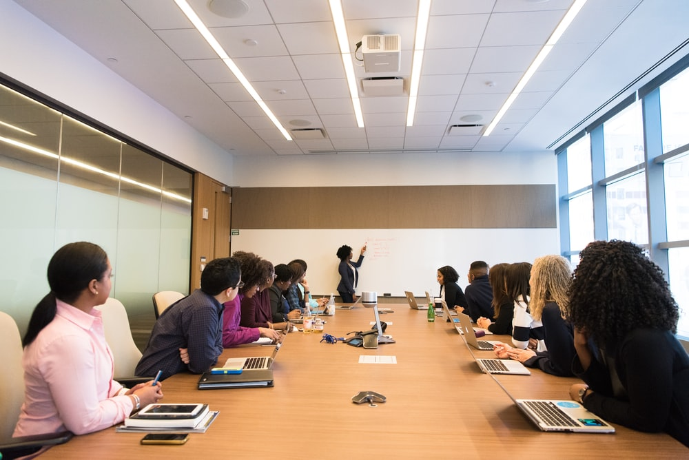 people on conference table looking at talking woman