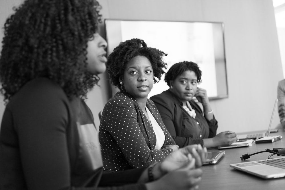 grayscale photography of two women on conference table looking at talking woman