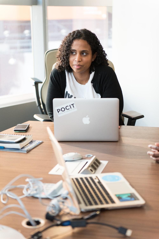 woman sitting beside laptop