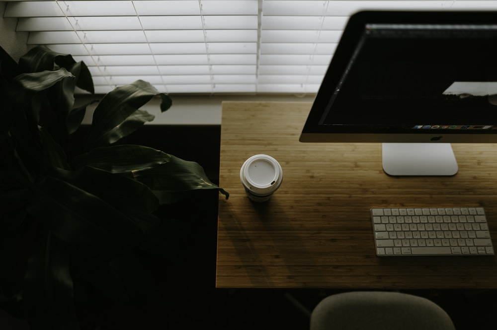 white coffee cup beside iMac