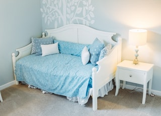 white wooden daybed beside table lamp