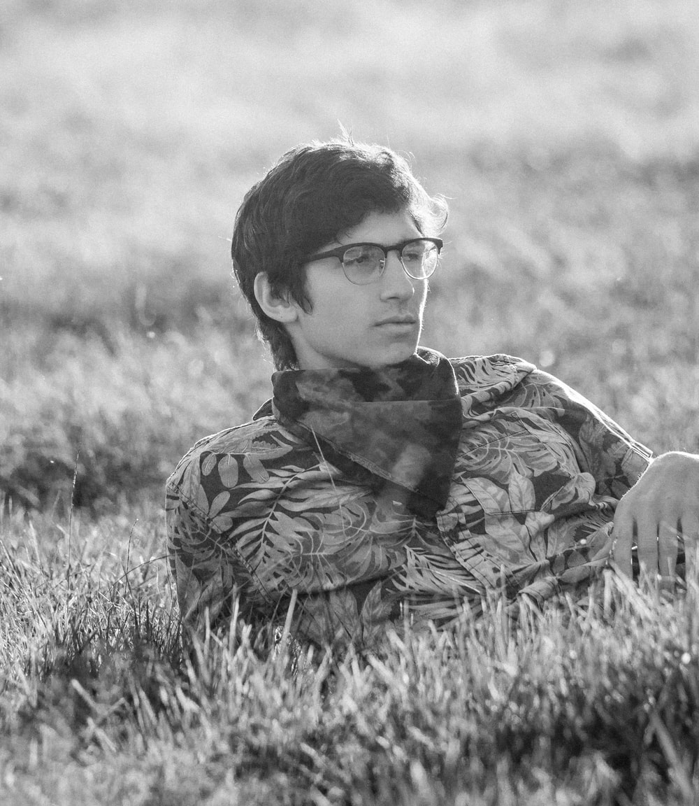 grayscale photography of man lying on grass