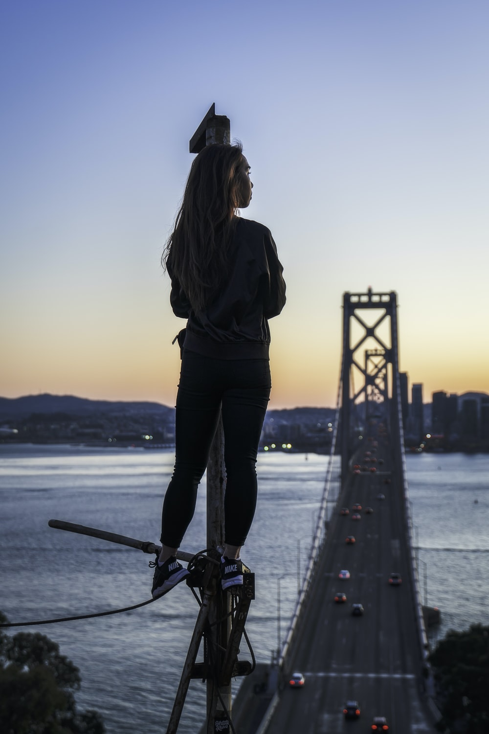 woman standing on metal pole looking at Oakland Bay Bridge during golden hour