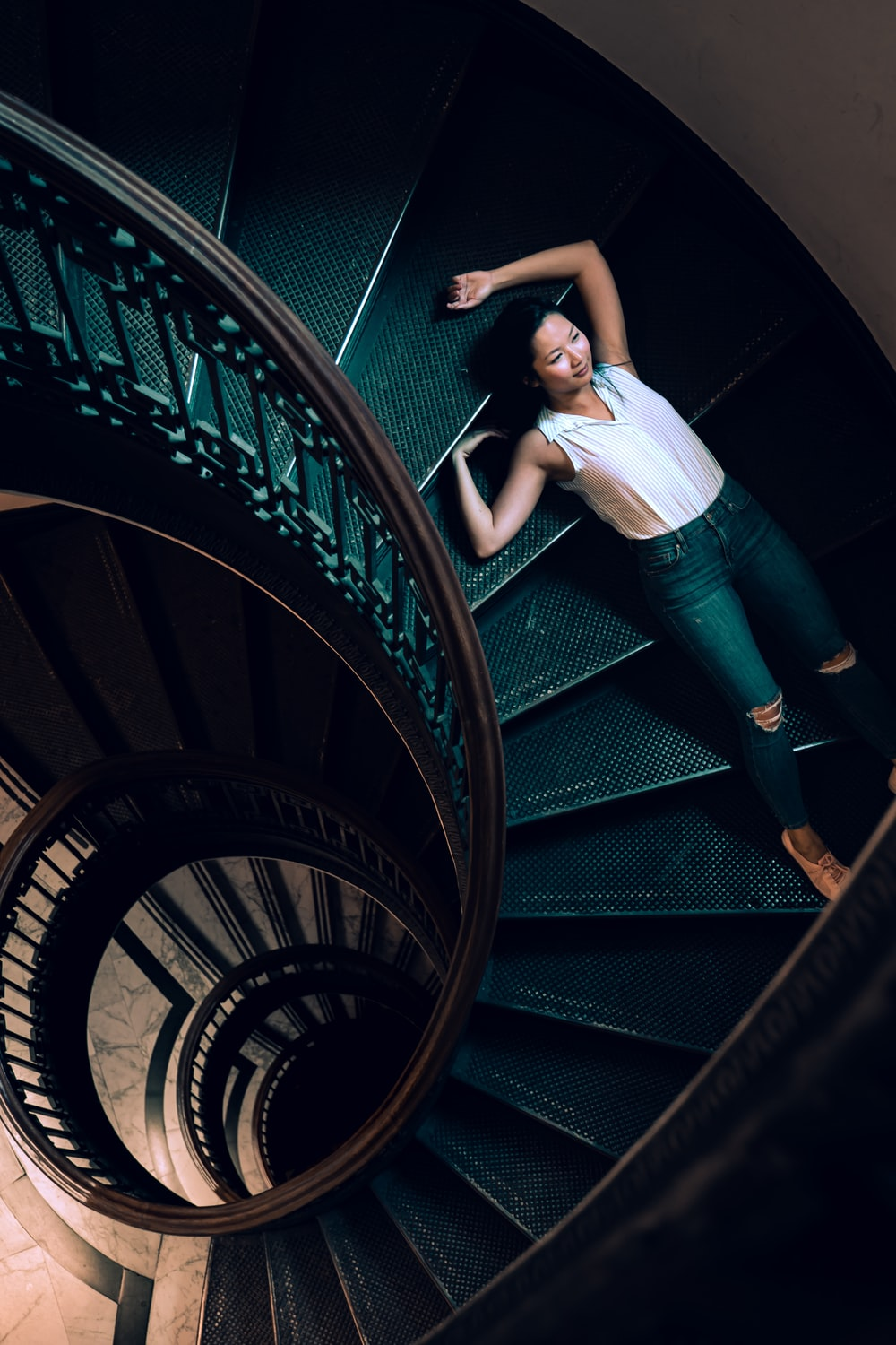 woman lying on gray stairs inside building