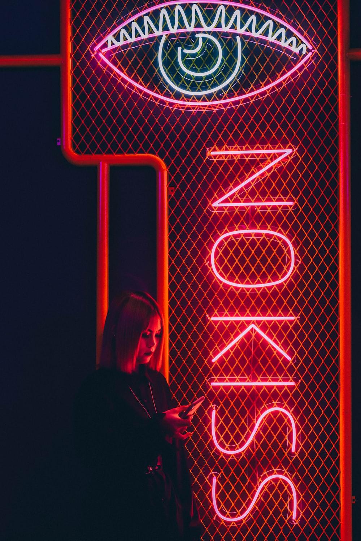 woman beside neon light signage