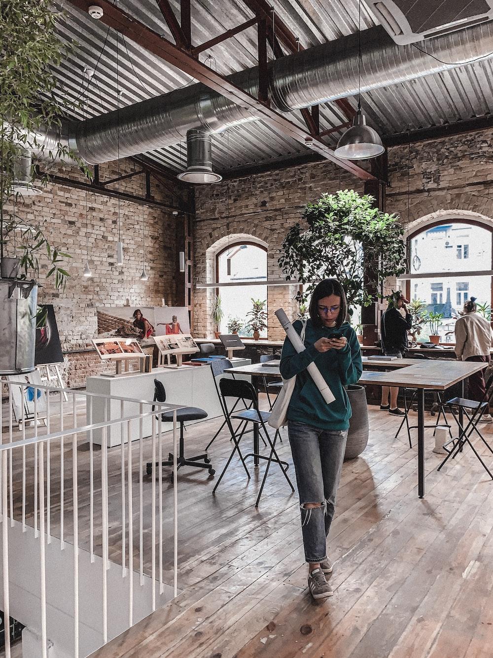 woman holding smartphone walking near table inside building