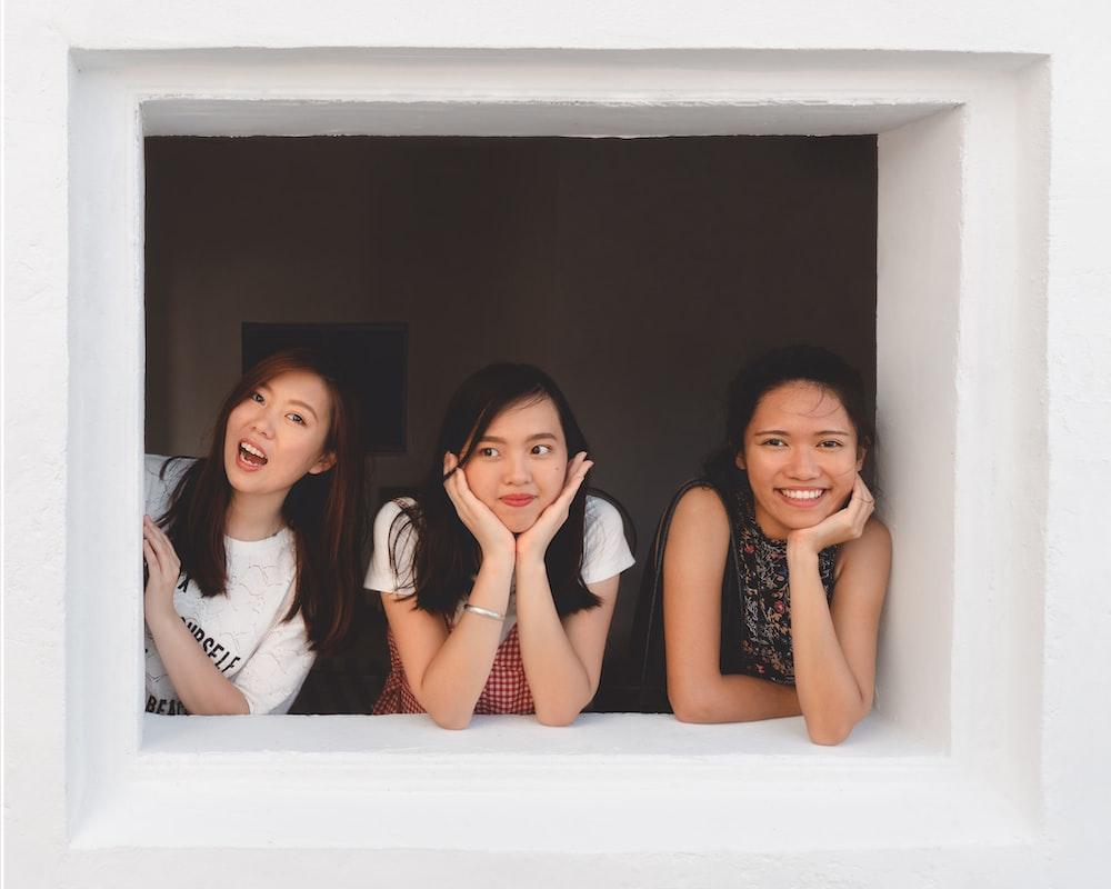 three smiling women at window