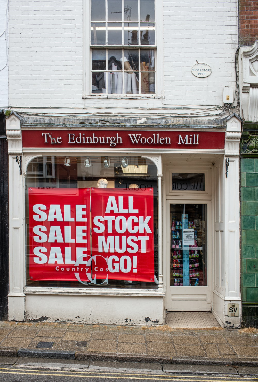 Sale Sale Sale and All Stock Must Go! signs on The Edinburgh Woollen Mill building windows during daytime