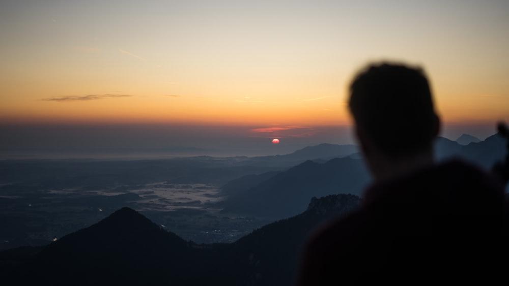 man facing mountain ranges